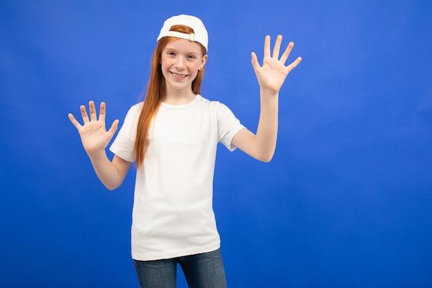Charmante fille adolescente aux cheveux roux dans un t-shirt blanc avec une mise en page montre dix doigts sur un fond bleu de studio.