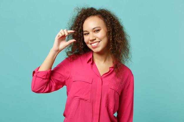 Charmante fille africaine en vêtements décontractés faisant des gestes démontrant la taille avec un espace de travail isolé sur fond de mur bleu turquoise en studio. concept de mode de vie des émotions sincères des gens. maquette de l'espace de copie.