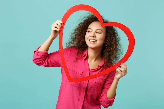 Charmante fille africaine en vêtements décontractés regardant de côté tenant un grand coeur en bois rouge isolé sur fond de mur bleu turquoise en studio. les gens émotions sincères, concept de style de vie. maquette de l'espace de copie.