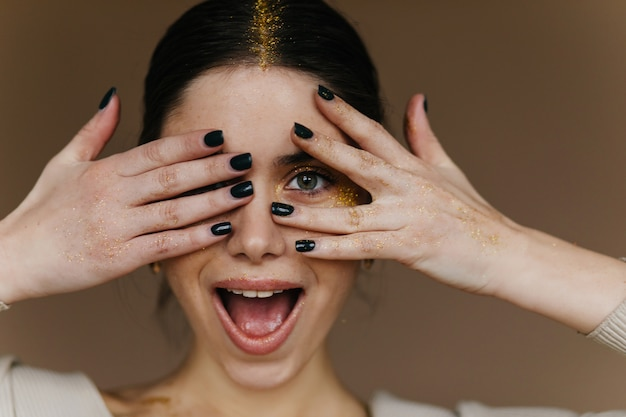 Charmante fille aux cheveux noirs posant avec un sourire surpris. jolie jeune femme aux cheveux noirs en riant
