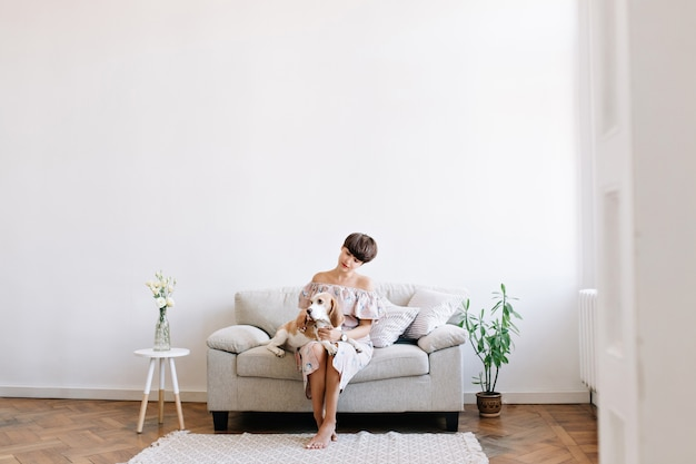 Charmante fille aux pieds nus assis sur un canapé gris entre petite table et plante verte, regardant chien beagle sur ses genoux