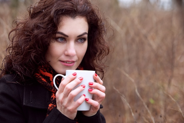Une charmante fille aux yeux bleus dans un manteau et un imperméable lumineux boit du café dans le parc par temps frais