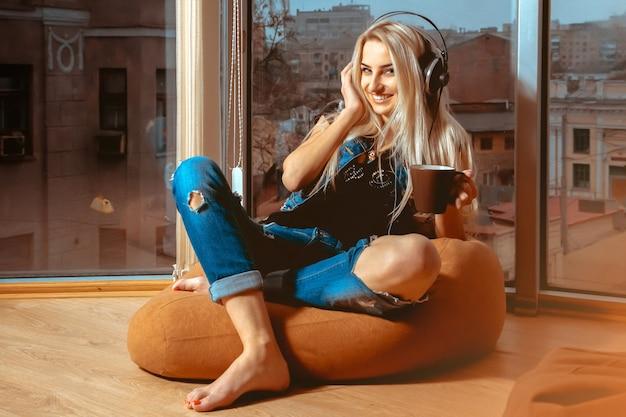 Charmante fille avec un beau sourire en écoutant la musique dans les écouteurs. concept de détente, de rafraîchissement et de loisirs