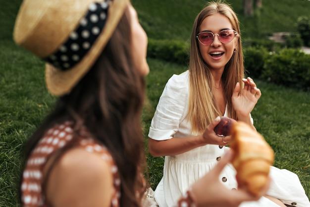 Charmante fille blonde aux cheveux longs en lunettes de soleil rouges et robe blanche tient une pomme, s'assoit sur un tapis sur l'herbe et parle à son amie brune bouclée