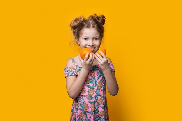 Charmante fille blonde dégustant des oranges en tranches posant dans une robe sur un mur de studio jaune