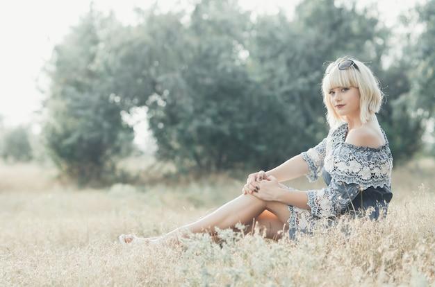 Charmante fille blonde avec des lunettes sur la tête en robe bleue sur fond d'arbres verts au coucher du soleil