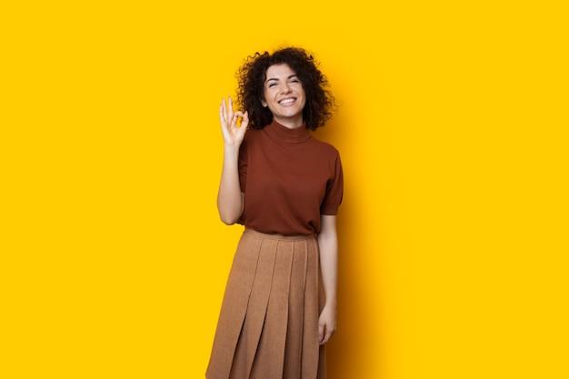 Charmante fille caucasienne aux cheveux noirs bouclés fait des gestes sur un fond jaune en souriant