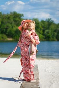 Une charmante fille dans une robe d'été légère se promène sur la plage de sable avec sa petite fille.