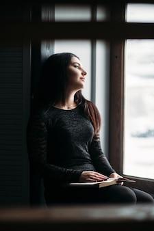 La charmante fille est assise sur le rebord de la fenêtre et tient un livre