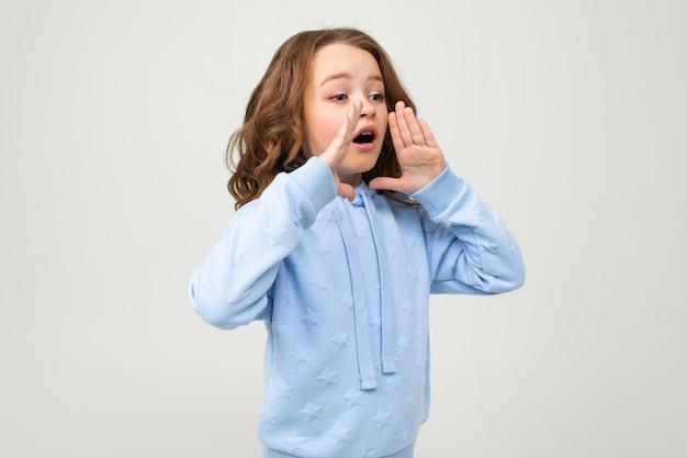 Charmante fille européenne dans un sweat à capuche bleu raconte les nouvelles tout en se tenant la main à la bouche sur un mur clair