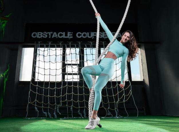 Charmante fille grande et mince est engagée dans une salle de sport avec des cordes