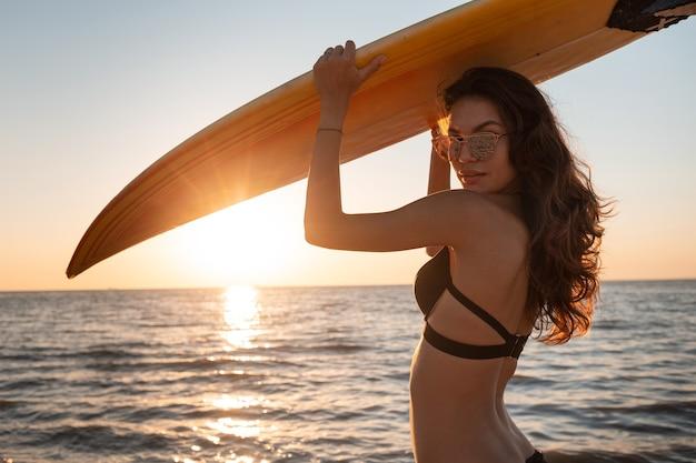 Charmante fille en maillot de bain noir tient une planche de surf au-dessus de sa tête sur la plage de sable près de la mer au coucher du soleil.