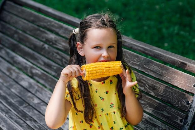 Une charmante fille mange de délicieuses vacances en famille de maïs sucré bouilli le week-end dans le parc de la ville