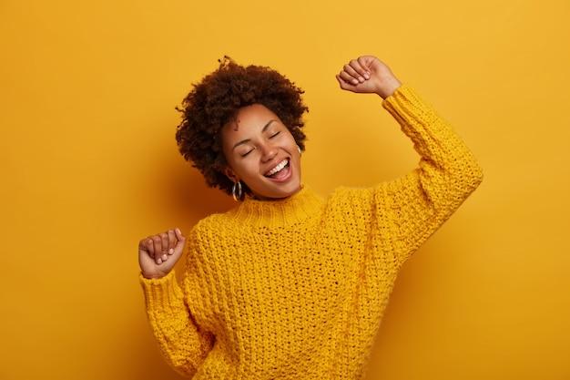 Une charmante fille à la peau sombre et animée danse joyeusement et célèbre la bonne nouvelle, se sent chanceuse et réussie