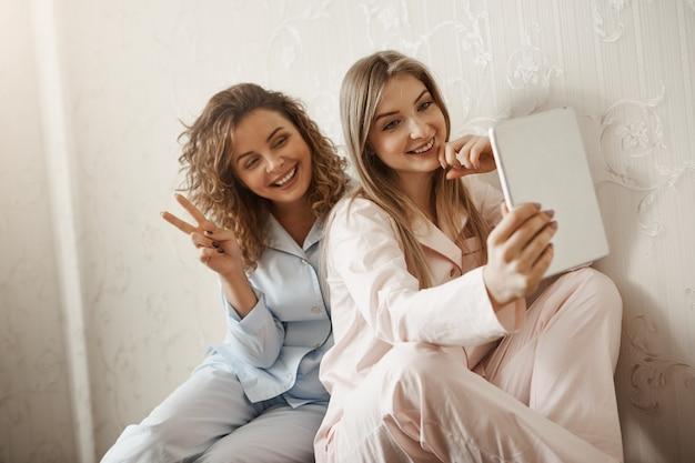 Charmante fille en pyjama prenant selfie avec maman à l'aide de tablette numérique