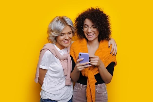 Charmante fille de race blanche aux cheveux bouclés et lunettes montre quelque chose au téléphone à son amie tout en posant sur un mur jaune