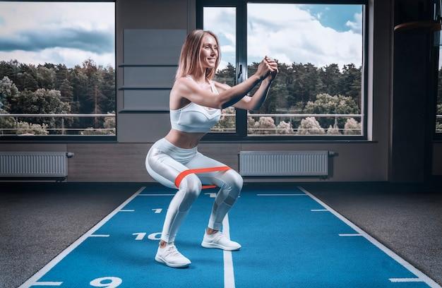 Charmante fille s'entraîne dans la salle de gym avec un élastique