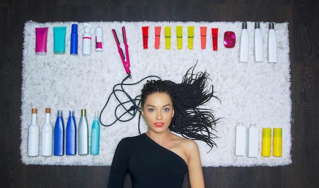 Charmante fille se trouve sur un tapis blanc comme neige. dans le contexte se trouvent des moyens cosmétiques pour le soin des cheveux.
