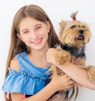 Charmante fille tenant un chien terrier isolé