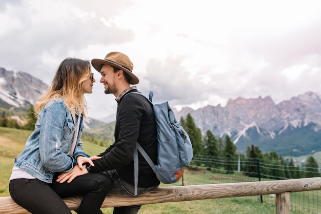 Charmante fille en veste en jean vintage se détendre avec son petit ami, passer du temps en plein air avec les montagnes