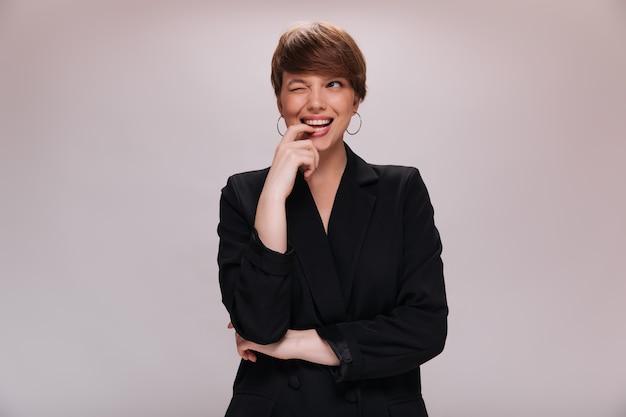 Charmante fille en veste noire clignotant sur fond isolé. femme aux cheveux courts en tenue sombre sourit sur fond blanc