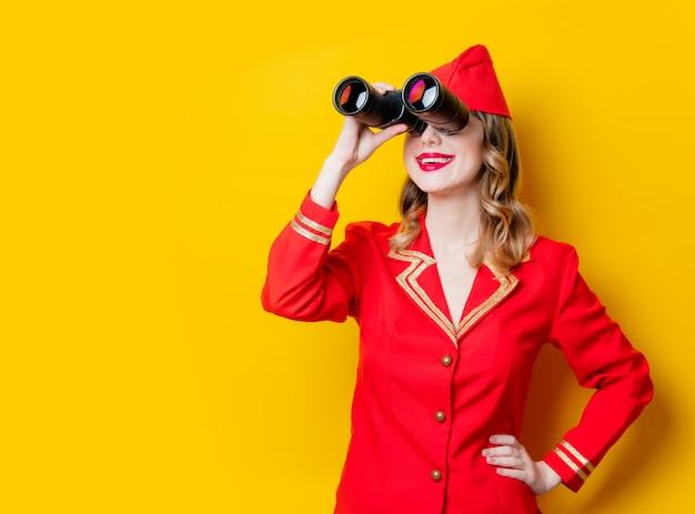 Charmante hôtesse vintage vêtue d'un uniforme rouge avec des jumelles