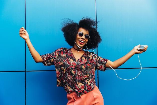 Charmante incroyable jeune femme afro américaine en lunettes de soleil, danse