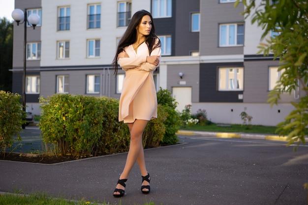 Charmante jeune brune dans une robe légère d'été, debout avec un sourire dans une rue de la ville