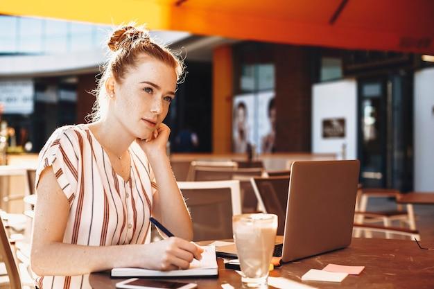 Charmante jeune femme d'affaires aux cheveux rouges et taches de rousseur en prenant des notes tout en buvant du café dans un café.