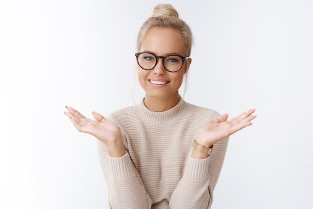 Charmante jeune femme d'affaires blonde créative dans des verres avec des cheveux peignés écartant les mains insouciante et indifférente se sentant heureuse et froide debout insouciante sur fond blanc, n'ayant aucun problème