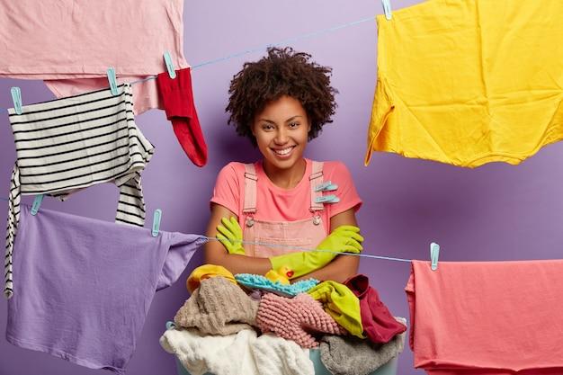 Charmante jeune femme avec un afro posant avec une lessive en salopette