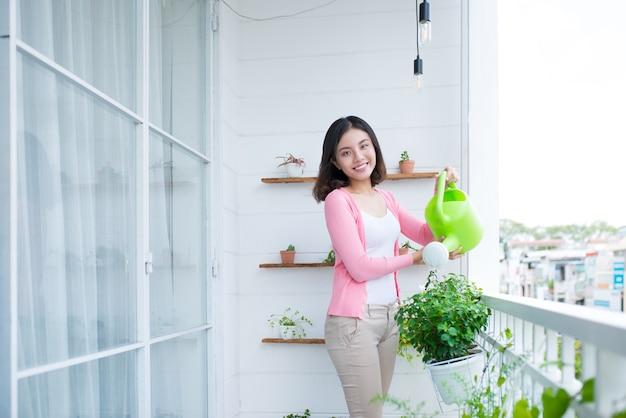 Charmante jeune femme asiatique arrosage des plantes en conteneur sur balcon jardin