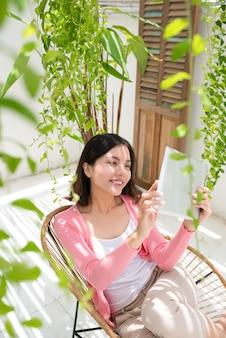 Charmante jeune femme asiatique détente sur balcon jardin