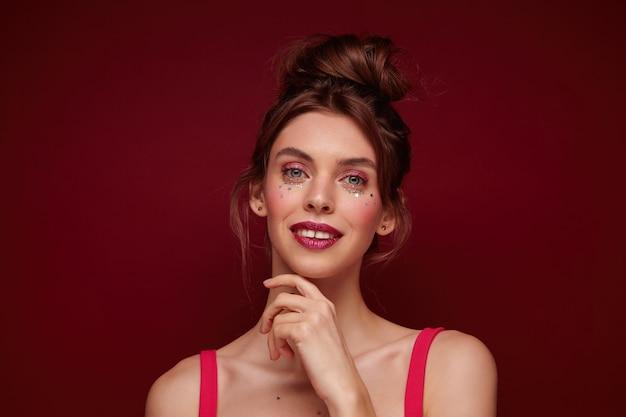 Charmante jeune femme aux cheveux bruns avec une coiffure en chignon portant du maquillage de fête tout en posant, regardant positivement et touchant doucement le visage