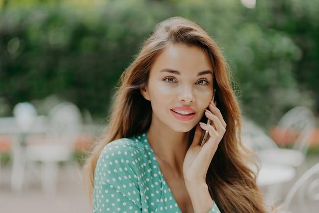 Charmante jeune femme aux cheveux longs, porte une chemise verte à pois et est assis à table dans un café en plein air