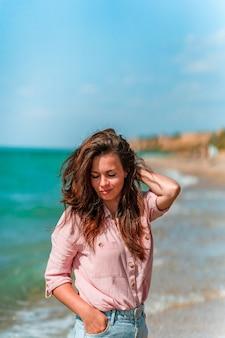 Une charmante jeune femme aux cheveux longs et vêtue d'une chemise se promène le long de la plage par une journée ensoleillée