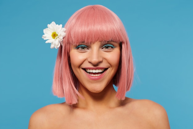 Charmante jeune femme aux cheveux roses romantique avec un maquillage coloré à la caméra et souriant largement, posant sur fond bleu avec de la camomille dans sa tête