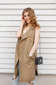 Charmante jeune femme avec un beau sourire dans un élégant vêtement élégant d'été posant et souriant près d'un mur en bois vintage sur une chaude journée d'été. jolie fille heureuse