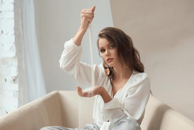 Charmante jeune femme à la beauté naturelle en blouse blanche élégante, pantalon gris et boucles d'oreilles tendance tenant du sable de mer qui coule d'une main à l'autre. la notion de transit du temps