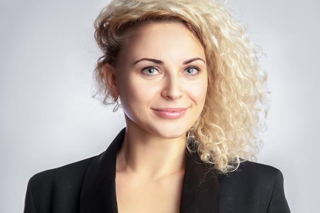 Charmante jeune femme blonde aux cheveux bouclés en studio sur fond gris en regardant la caméra