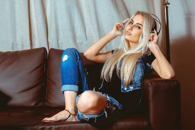 Charmante jeune femme blonde écoutant de la musique dans les écouteurs et posant sur le canapé. concept de détente, de rafraîchissement et de loisirs