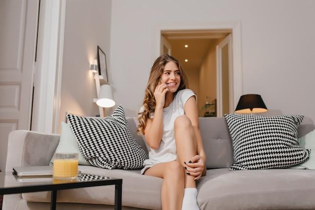 Charmante jeune femme brune assise sur le canapé et parler au téléphone