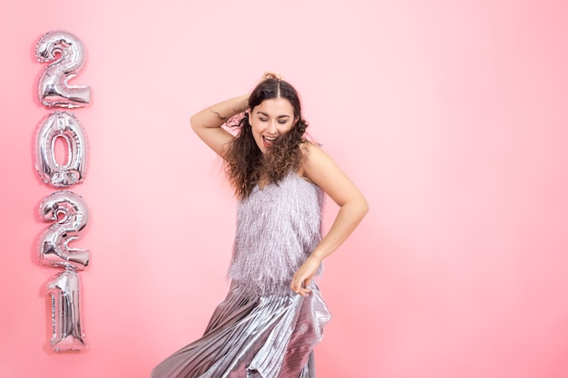 Charmante jeune femme brune aux cheveux bouclés dans une tenue de fête argentée dansant sur un mur rose avec des ballons d'argent pour le concept de nouvel an