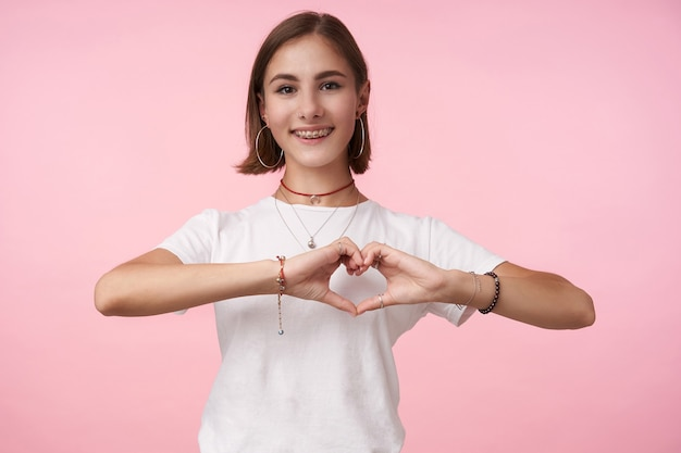 Charmante jeune femme brune aux cheveux courts gaie avec maquillage naturel formant coeur avec les mains levées et souriant largement à l'avant, debout sur le mur rose
