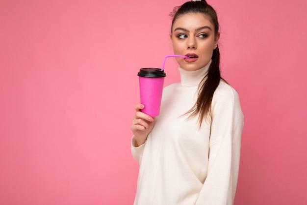 Charmante jeune femme brune heureuse et réfléchie portant des vêtements élégants isolés sur un mur de fond coloré tenant une tasse en papier pour une maquette buvant un milk-shake regardant sur le côté. espace de copie
