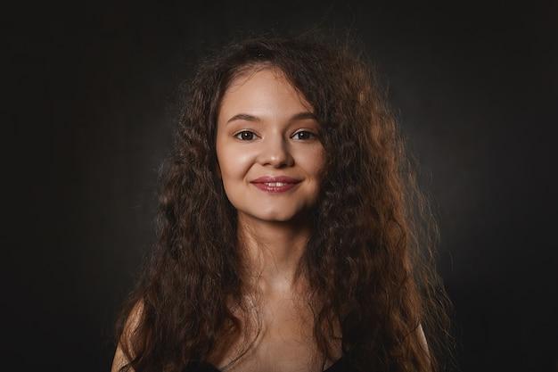 Charmante jeune femme brune joyeuse avec une coiffure volumineuse bouclée et une peau parfaite souriant joyeusement, heureuse de bonnes nouvelles positives, exprimant la joie. jolie fille aux cheveux lâches foncés posant