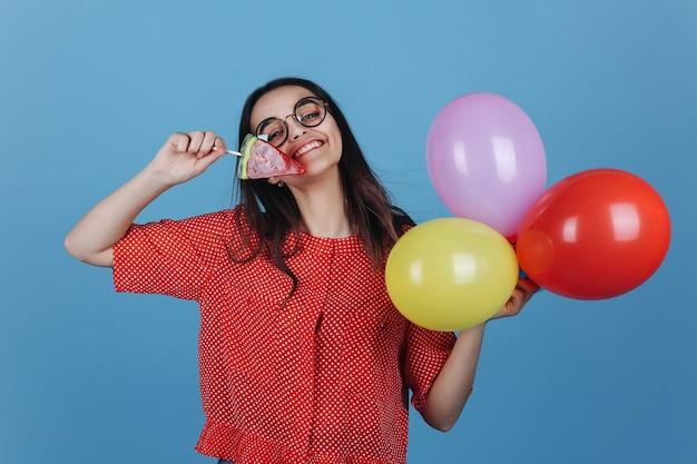 Charmante jeune femme brune se dresse avec une sucette et des ballons