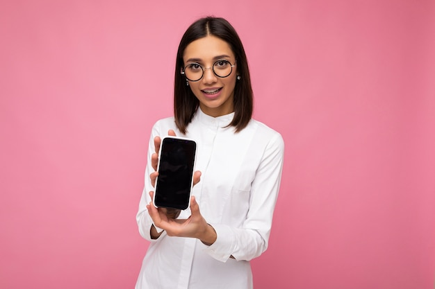 Charmante jeune femme brune souriante portant un chemisier blanc et des lunettes optiques debout isolée sur fond rose montrant un téléphone portable avec un écran vide pour une maquette regardant la caméra