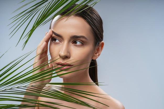 Charmante jeune femme debout derrière une plante verte