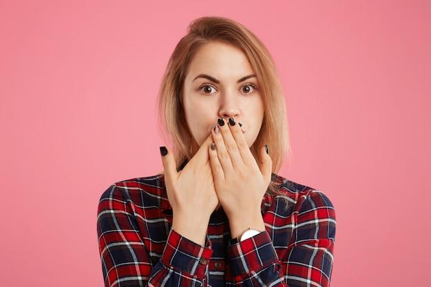 Une charmante jeune femme essaie de garder le silence, pas de bavarder et de dire que des informations confidentielles ont couvert sa bouche de ses mains